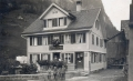 Foto 109 - Bi z'Karis vor Haus- und Ladeneingang ca. 1924 Handlung und Bäckerei Karl Aschwanden Bergführer